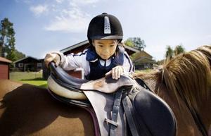 8-åriga Alicia Olofsson från Sommarhagen får hjälp upp på sin häst inför ett ridpass där hon ska träna hoppning.