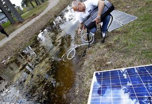 Bengt Skörelid bjöd på vatten från dammen bakom Teknikparken. Ett stillastående vatten som inte ser vidare gott ut. Reningsapparaten ligger på gräskanten och pumpen drivs av solceller.