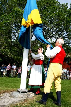 Flaggan firas upp i toppen på Folkärna Gammelgård.