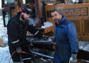 Martin och Bo Sjöberg, Brynjegård, arbetade i måndagens kyla med vägen till den havererade timmerskördaren.Foto: Ingvar Ericsson
