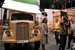Filminspelning pågår. En stor del av inspelningen av filmen Hvidstensgrruppen är gjord i studio i Köpenhamn. Skådespelerskan  Marie Bach Hansen ses vid bilens vänstra flygel.