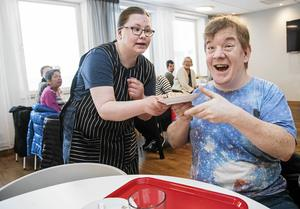 Ronja Borglund serverar en förväntansfull Rasmus Östman en rulltårtsskiva.