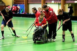 Fredrik Sundin sitter i rullstol och behöver hjälp av sin assistent, Lasse Hellström, för att kunna delta i matchen.