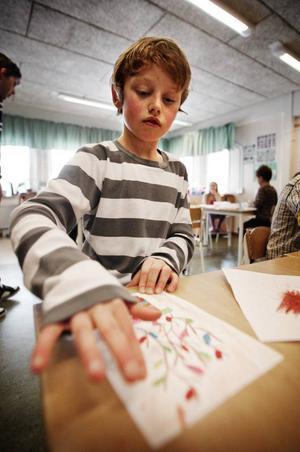"""Jesper Lindberg, 9, har ritat påskris.Klassen Sylarna 2–3 är klara med sina bidrag till årets Påsk i Färg. Längs fram ser vi Kalise Lundin, 9, som visar upp en av sina teckningar. """"Jag tycker om snygga kycklingar"""", säger Kalise."""