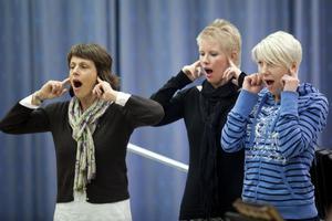 Nina Pergament, Frida Björnerstedt och Karin Enocksson håller koll på den lilla gropen vid örat under uppvärmningen med Roslagens vokalensemble.