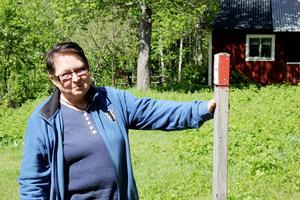 Birgit visar hur stolparna ser ut som märker ut vandringsleden.