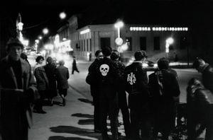 Stora gatan i Västerås i mitten 1950-talet. Ett gäng knuttar med skräckinjagande dödskalleemblem på skinnjackorna har samlats kring en motorcykel.