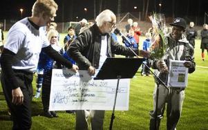 Sporthallschefen Peter Hoxell och Ingvar Henriksson (S) uppvaktar 2013 års mottagare av Kobban-priset, LFK:s pojklandslagsspelare Junior Kamana. Foto: Dennis Pettersson/DT