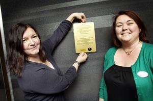 Tina Meurk på Hogges håller upp tavlan, bredvid henne står alkoholhandläggaren Marika Almström.