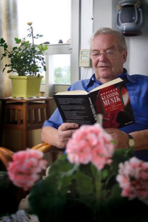 Sven Carlsson sitter på sin balkong och läser en bok om klassisk musik. FOTO: Lovisa Granberg
