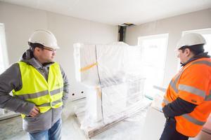 I lägenheterna har byggarbetarna redan lyft in de färdiga köksluckorna och fläkten.