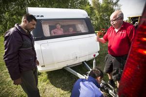 Nikosjor får hjälp av kyrkans vaktmästare Bertil Hargemark att haka på husvagnen på bilen för färd till den nya boplatsen. Barnen Stefani och Louis, som syns i fönstret, längtar efter att få ta lekplatsen vid Ängsmokyrkan i besittning.