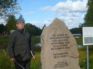 Guiden Stellan Fagrell och minnesstenen från branden som stårpå Kårböle skans.