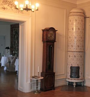 Vid ingången till den stora salongen finns en av herrgårdens vackra kakelugnar.