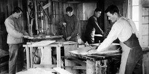 På en av snickeribilderna finnms årtalet 1918, vilket skulle kunna innebära att fotot är drygt etthundra år gammalt. Men var är det taget, vilka är snickarna och vad tillverkar de?