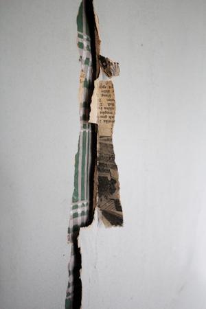 Flera lager av tapet och tidningspapper i väggen.