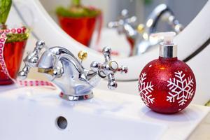 Inte ens handfatet på toaletten blir julfritt. En tvålpump i form av en julkula smälter elegant in. Foto: Lennye Osbeck