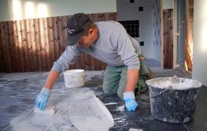 Byggarbetaren Kennet Andersson håller på att göra klart golven  i kontorsbyggnaden.