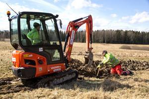 Är det stenigt krävs en liten grävmaskin för att komma ner till rätt djup. Linus Wallin kör maskinen och Emil Johansson pekar var han ska gräva.