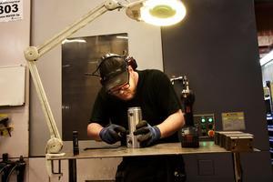 Robin Löfgren  med en sviveltapp som ska bearbetas. I bakgrunden en av flera fräsmaskiner som används i maskinbearbetningen av gjutna metalldelar från kunder.