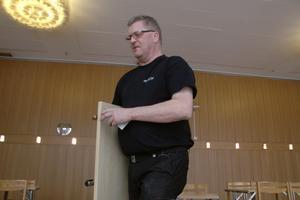 """Anders Strand, vaktmästare i Kulturhuset tio14, röjer och fäller ihop möbler med van hand. """"Jag har roligt på jobbet. Och nu slipper jag oroa mig och vet att jag har en inkomst."""""""