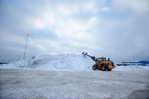 Snödeponin är bemannad med personal som ser till att snömassorna från lastbilarna hamnar rätt.