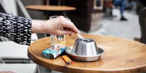 Sedan 1 juli är det slutfimpat på uteserveringar. Kommunen borde låta sommarjobbare dela ut fickaskkoppar till förbigående rökare, menar debattörerna.