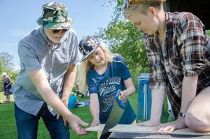 Först ska Eli såga bitarna till växtpressen. Morfar Jan vill ha ett finger med i spelet. Matilda från Naturskolan håller i.