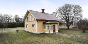Mest klickad. Huset har en öppen utsikt mot gärden och skog och ligger i byn Frändesta i Romfartuna socken. Foto: Länsförsäkringar Fastighetsförmedling