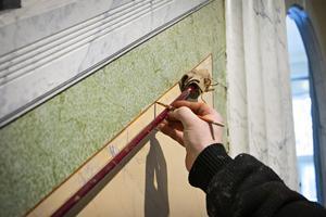 Med endast en målarkäpp som stöd målar Kaj Halminen dit de sista linjerna i marmormålningen.