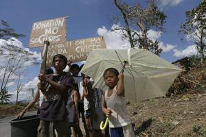 Barn ber förbipasserare om donationer. Tyfonen Bopha har gjort minst 300 000 människor hemlösa. Filippinerna vädjade förgäves på klimatmötet i Doha om snabba åtgärder för att bromsa temperaturhöjningen.
