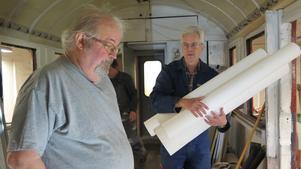 Örjan Zakrisson kommer med väv som ska limmas upp på väggarna i korridoren. Bengt Lindberg måste beställa mer.