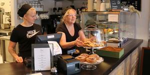 Emma Jensen står i kassan på restaurangen medan Maija Jensen lagar maten.