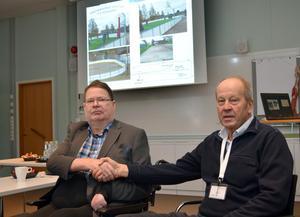 P-O Ejendal, till vänster, och Anders Niss bekräftar med ett handslag överenskommelsen om att P-O sponsrar projektet Västanviks Arena, en is- och boulebana, men en miljon kronor ur egen ficka. Bakom dem syns bilder på hur anläggningen ska se ut.