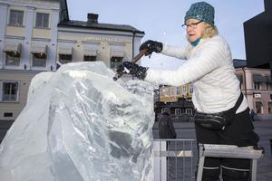 Lena Kriström skulpterar isen med ett Isjärn.