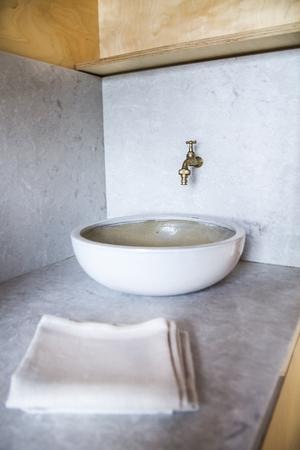 Till lofthuset fraktas dunkar med färskvatten, så att det finns rinnande vatten från handfatet.