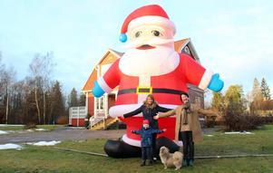 Tomtekram från stora och små. Walter, Helena och Helene Howie framför den imponerande tomten. Hunden Aston tittar på.