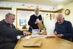 Gunnar Ennerstam, Ann-Marie Lundman och Roland Persson packar papperspåsar med tandkräm, tandborste och en chokladkaka.