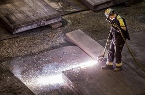 En bild från ett stålverk där en arbetare kontrollerar eventuella sprickor i stålet och skär bort kanter. Foto: Marcus Ericsson/TT