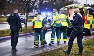 Ambulanspersonal bär den skadade kvinnan till den väntande ambulansen.