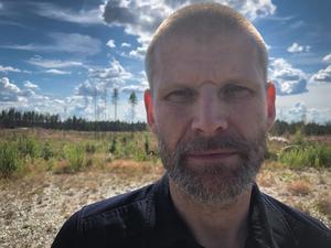 Fredrik Eriksson tror att den exakta startpunkten för branden ligger någonstans vid de två tallar som skymtar i bakgrunden på bilden.