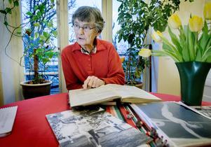Karin Lindén läser i Olympiaboken för 1948. Där syns svart på vitt hur män omnämns för sina individuella resultat i  gymnastik –men inte en enda kvinna. Även om de vann sin gren – som Karin. Nu tar hon strid för sin sak – och har skrivit till IOK för att få sin guldmedalj.