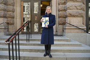 Finansminister Magdalena Andersson (S) ståendes med vårbudgeten framför riksdagen.Foto: Henrik Montgomery / TT.
