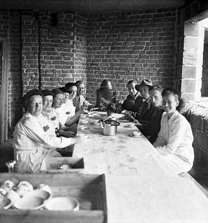1948. Arbetare fikar vid taklagsfesten för Östra Vintergatan i Rosta. Bildkälla: Örebro stadsarkiv/fotograf okänd.