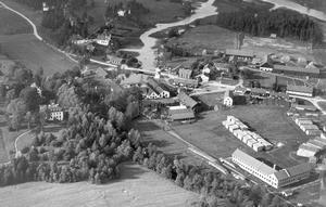Flygfoto över Vedevåg, de båda kyrkogårdarna ligger i bildens överkant på var sin sida om Borsån västra flöde. År troligen runt 1930. Bild: Lindesbergs kulturhistoriska arkiv