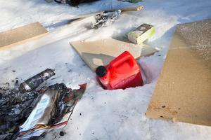 Spånskivor, tidningar och spillolja i plastdunk hittades kastat i naturen.
