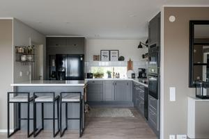 Köket har öppen planlösning mot vardagsrummet och matrummet. Förutom traditionella vitvaror finns det även en vinkyl. Foto: Utsikten foto.