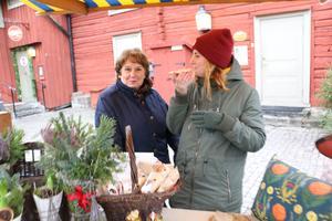 Maria Granlund och Margareta Granlund tar en smörgås innan julmarknaden kommer igång på allvar.