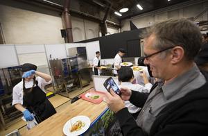 Mikael Reitan, kocklärare på Polhemsskolan, tar en bild på Isabelle Nilsson som pustar ut.
