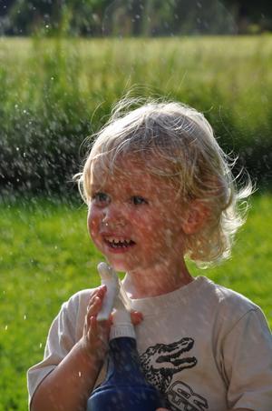 Alexander 2,5 år leker med vattensprutan hos farmor i Enköping.